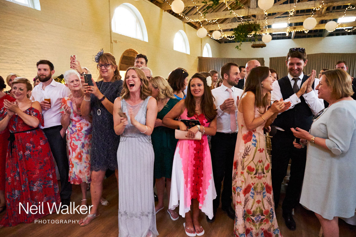 guests laugh & clap at the bride and groom's first dance