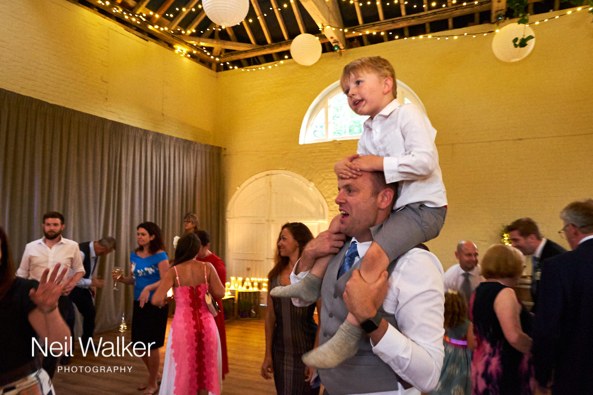 a small boy on his father's shoulders at a Sussex wedding