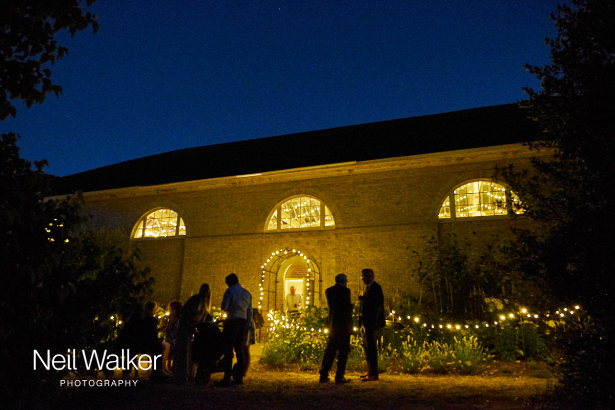 the outside of the Georgian Riding School at Firle, at night during a wedding