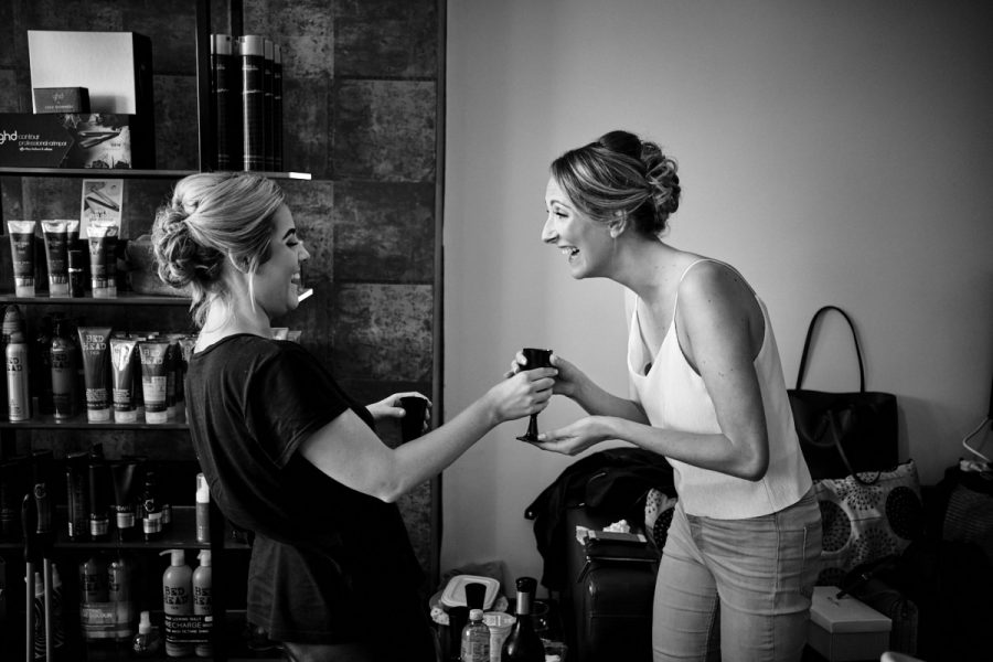 Bridesmaids laughing while they have their hair and makeup done for the wedding.