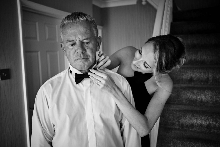 The father of the bride getting help with his bow tie from a bridesmaid.