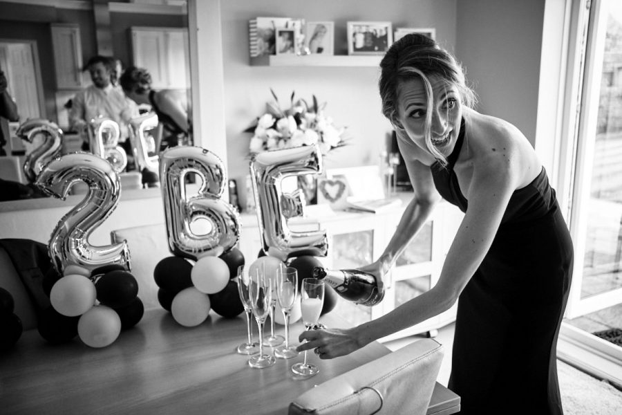 A bridesmaid pouring champagne.