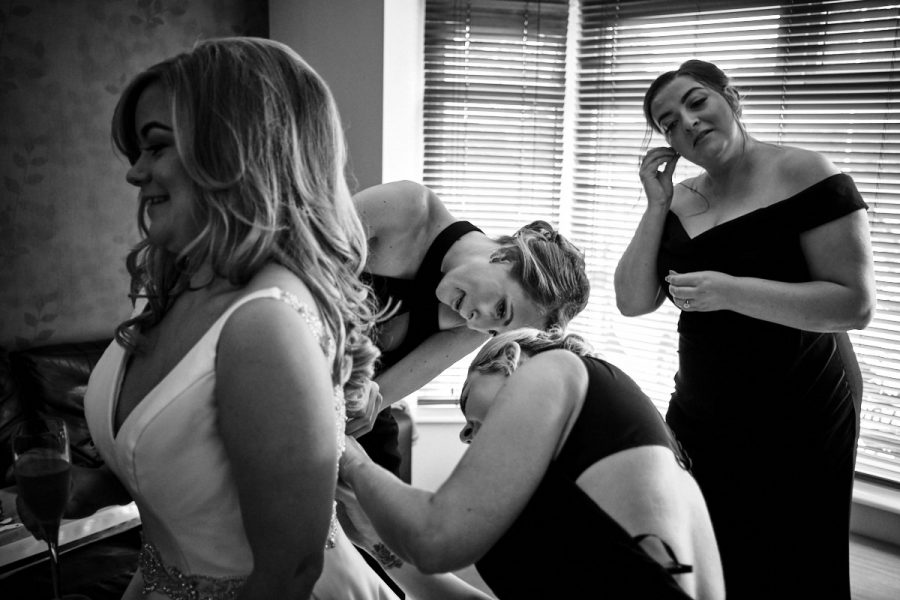 The bridesmaids helping the bride to do up her dress.