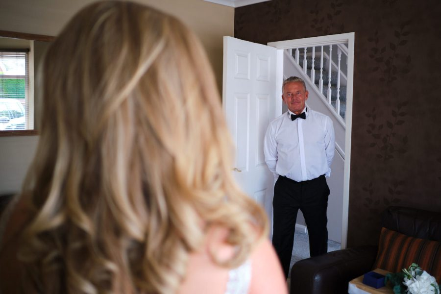 The bride's father seeing her in her wedding dress for the first time.