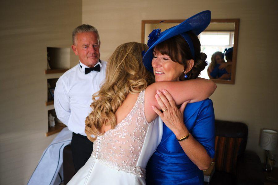 The bride hugging her mother before her wedding.