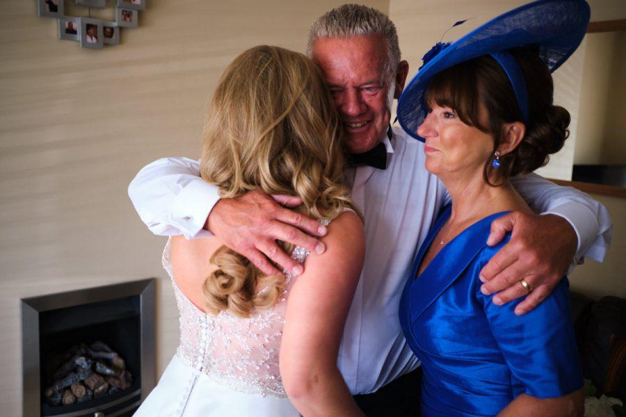 The bride hugs her mum & dad before her wedding.