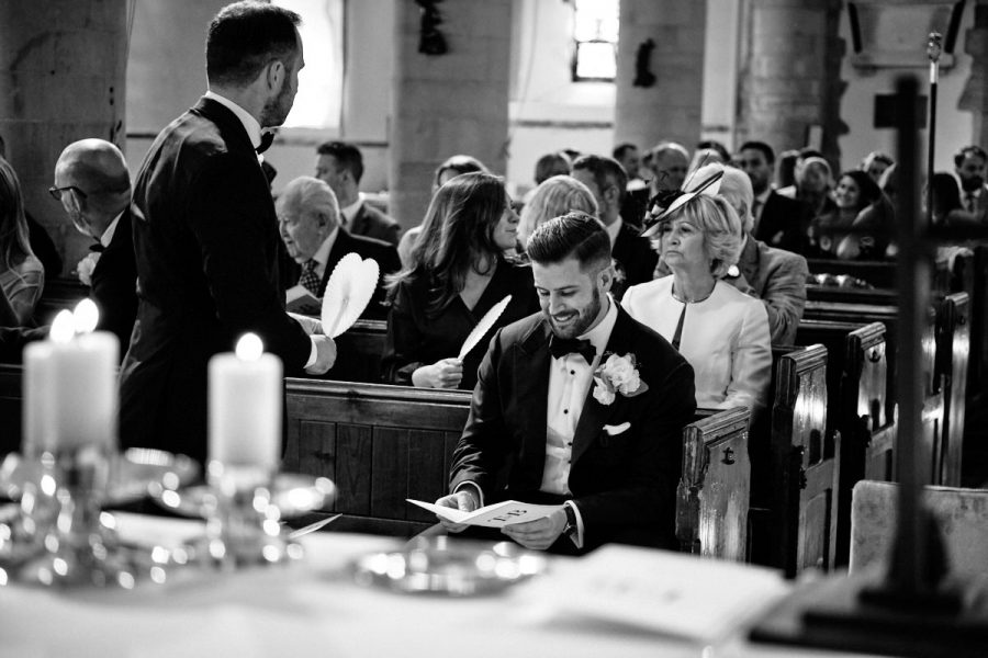 The groom smiling while he waits for his bride to arrive at church to get married.