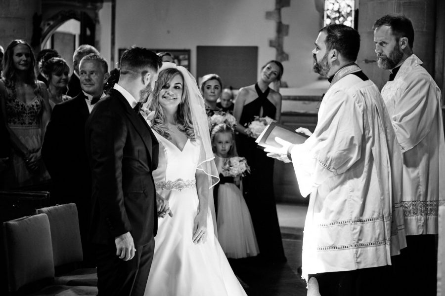 The bride and groom in church looking at each other.