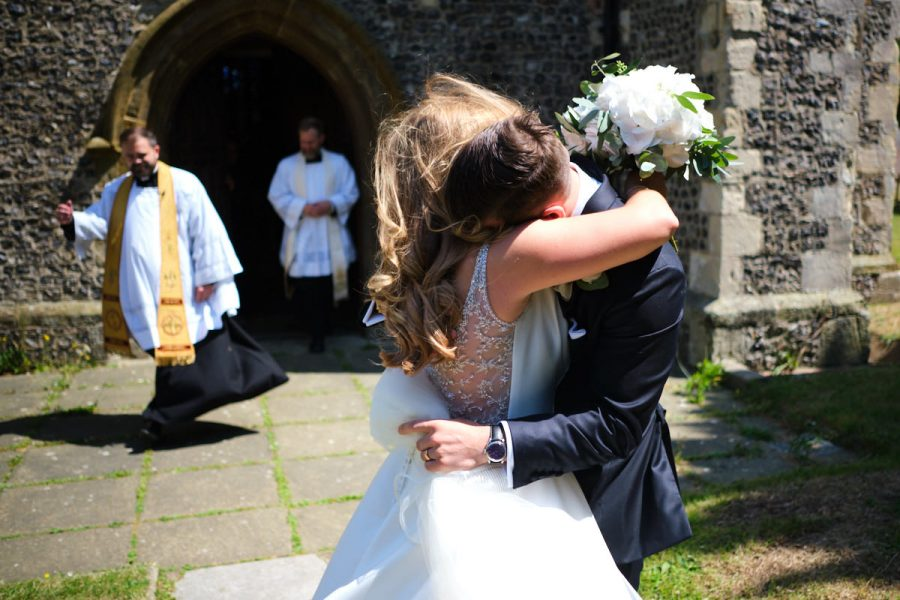 The bride and groom hugging outside the church.