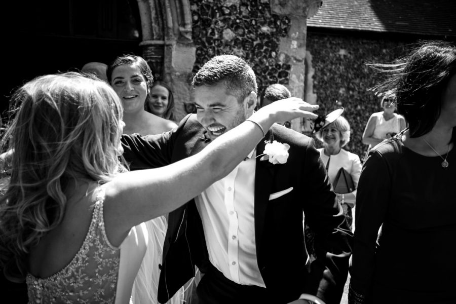 The bride being congratulated by the best man.