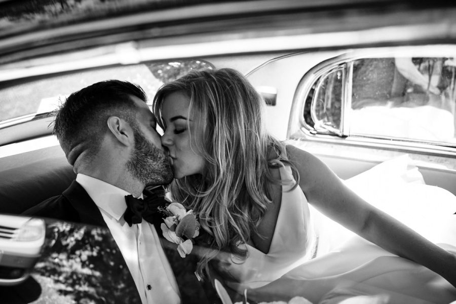 The bride and groom in the wedding car.