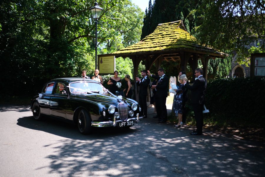 The bride and groom leaving the church in the wedding car.