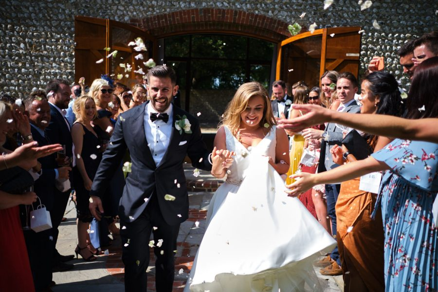 The confetti run at a wedding at Cissbury Barns, photographed by Sussex wedding photographer Neil Walker.