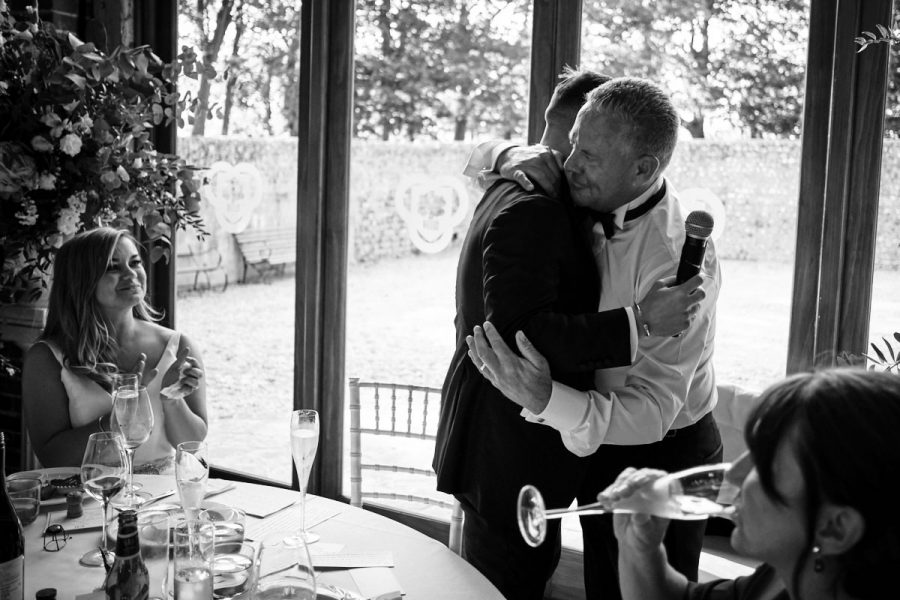 The groom hugging the bride's father.