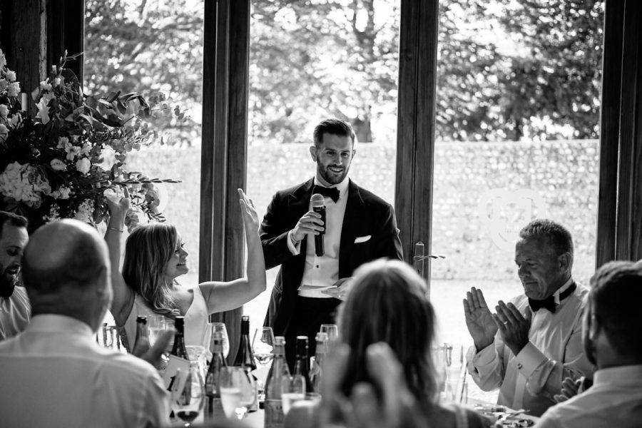 Guests cheering during the groom's speech at a wedding at Cissbury Barns in Sussex.