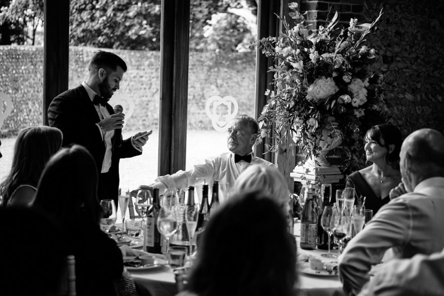The bride's father looking at the groom while he reads his speech.