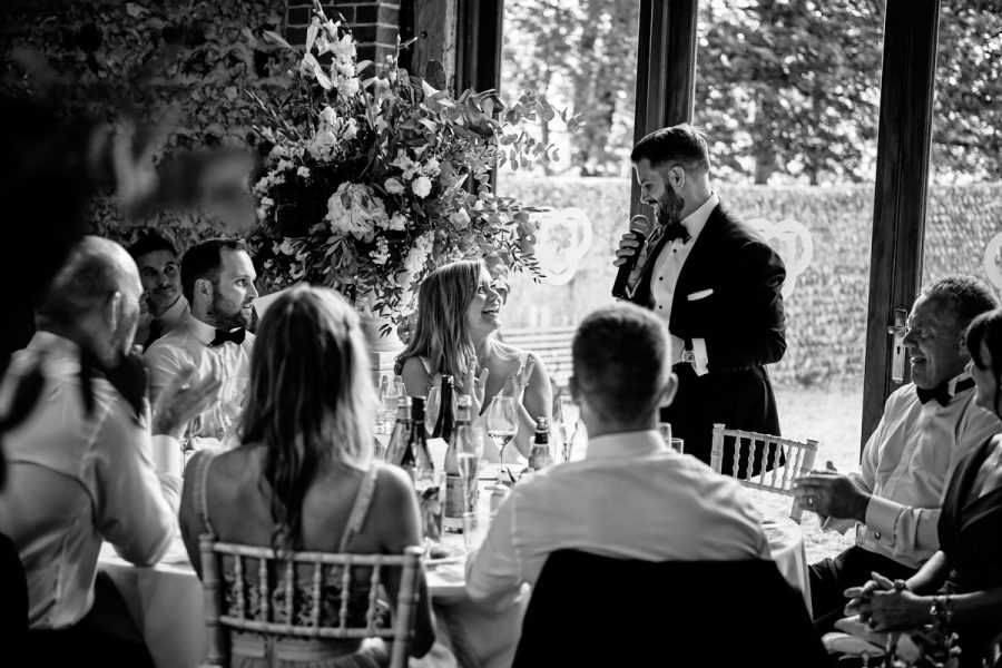 The groom looks at the bride during his speech.