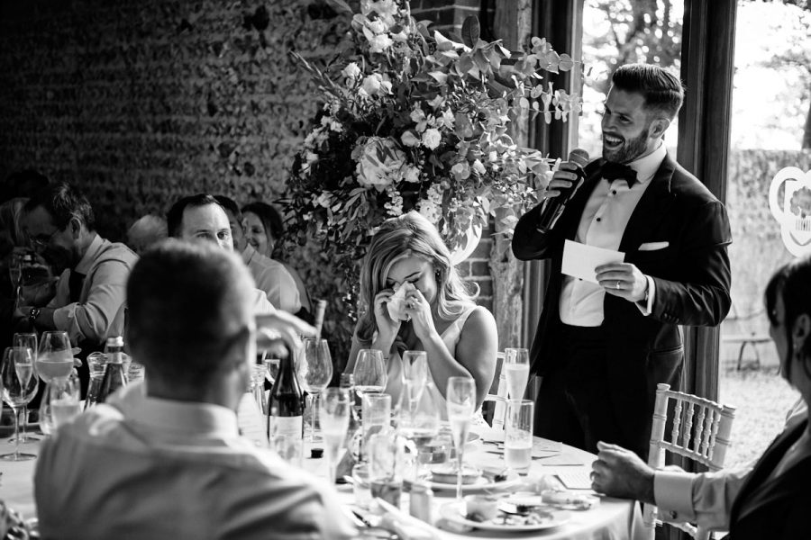 The bride cries while the groom does his speech