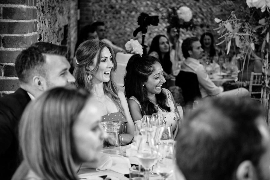 Guests laugh during the best man's speech.