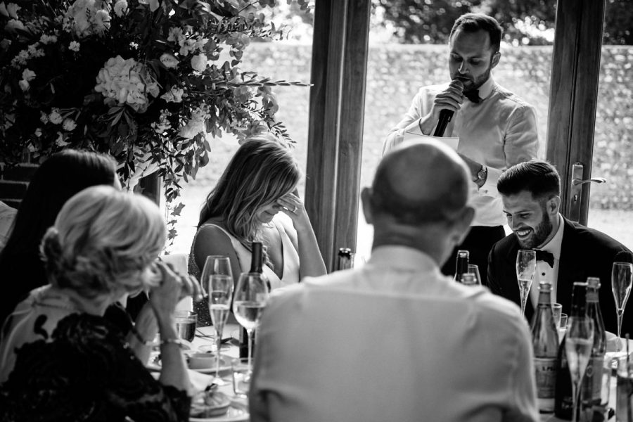 The groom and bride laugh during the best mans speech.
