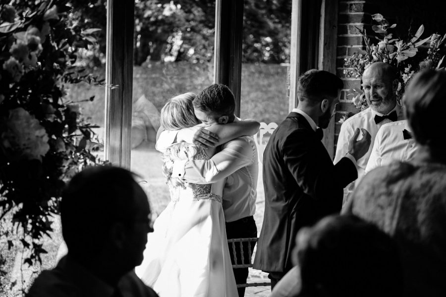 The best man and the bride share a hug.