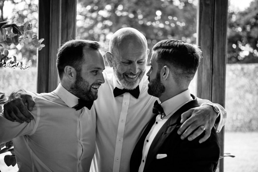 Father of the groom and his sons enjoying a hug together.