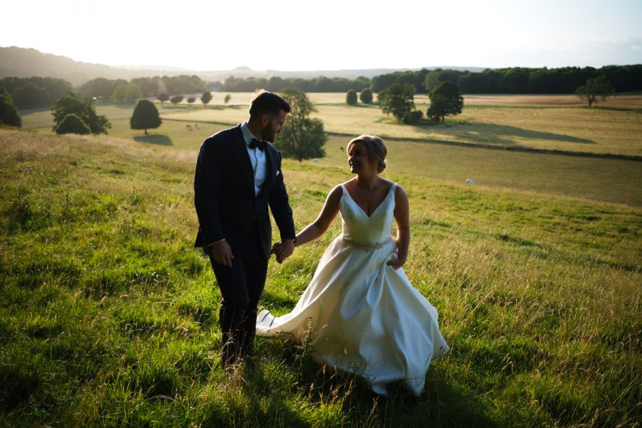 The bride and groom walking across the South Downs on the day of their wedding photographed by Cissbury Barns wedding photographer Neil Walker.