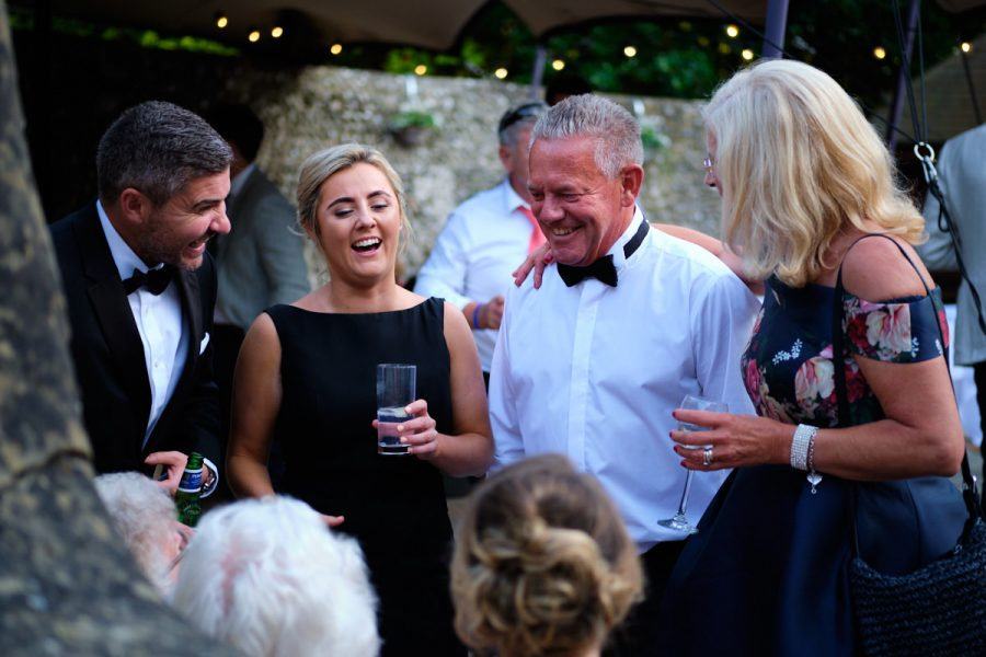The bride's father talking with guests at a wedding in Sussex.