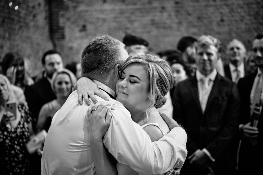 The bride hugging her father at her wedding.