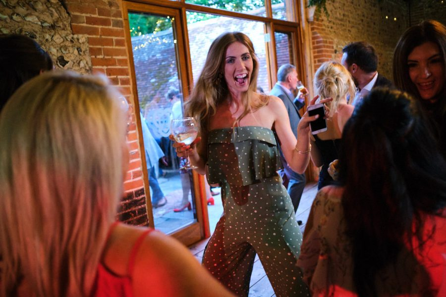 A guest dancing at a wedding at Cissbury Barns in Sussex.