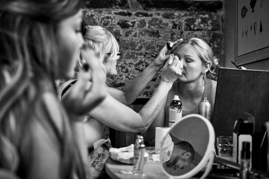 The bride at a wedding at Grittenham Barn in Sussex having her makeup done.