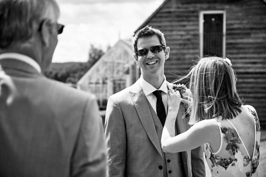 A groomsman having his buttonhole put in