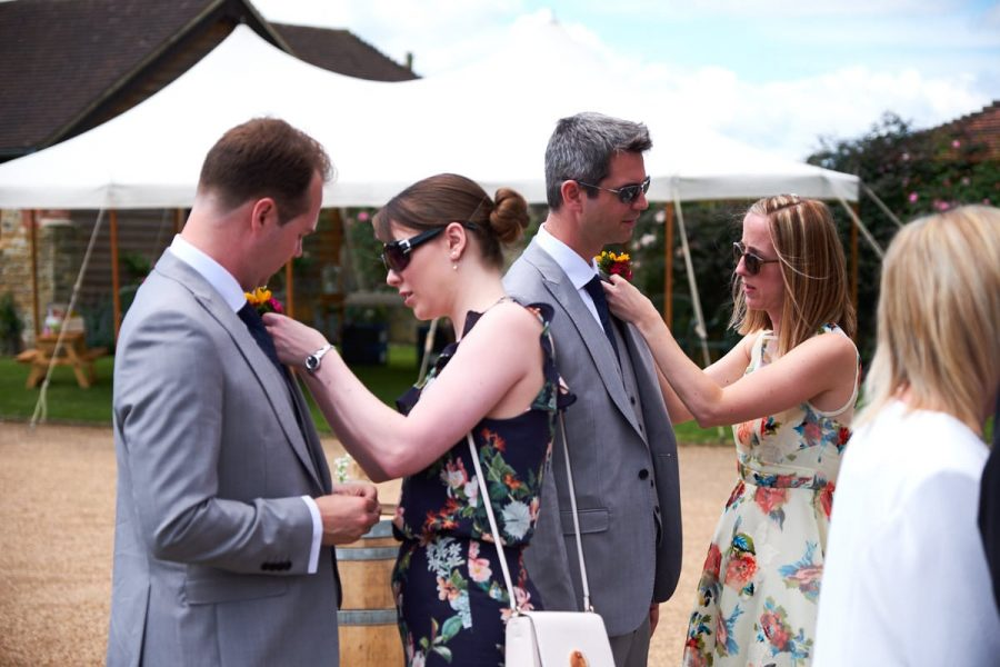 Groomsmen at a Sussex wedding having their buttonholes put in