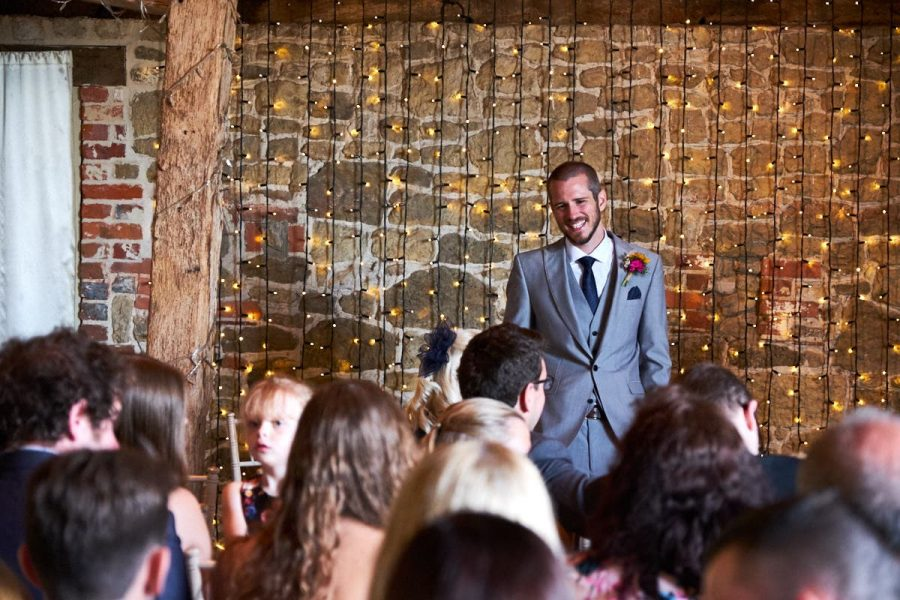 The groom waiting for his bride in the ceremony room at Grittenham Barn