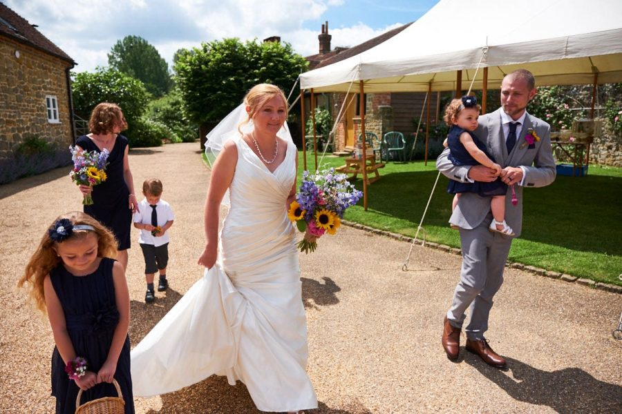 The bride walking to the ceremony room at Grittenham Barn
