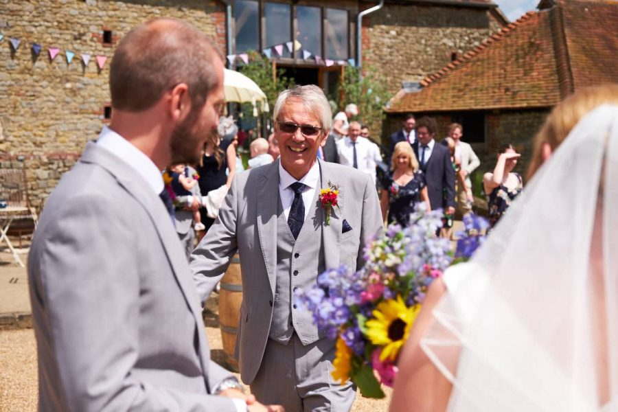 The groom's father coming to congratulate the happy couple