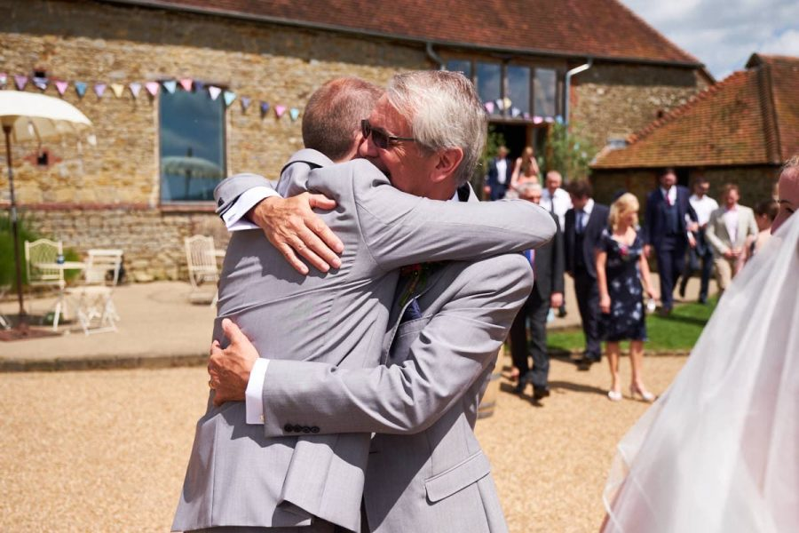 The groom's father hugging the groom