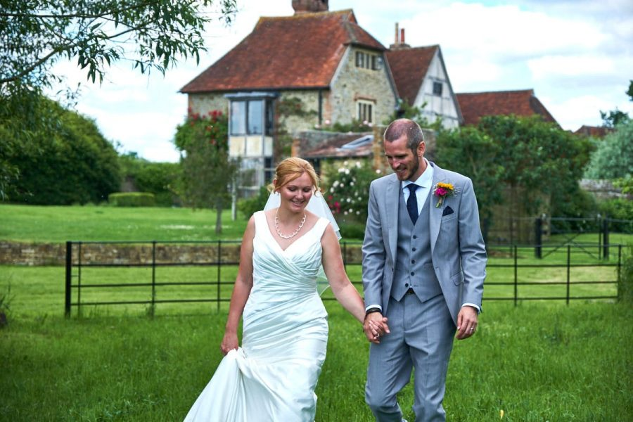The bride and groom walking in front of the farmhouse at Grittenham Barn