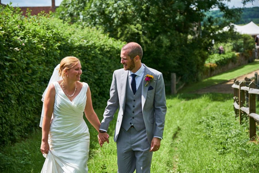 The bride and groom walk together at their wedding at Grittenham Barn in Sussex