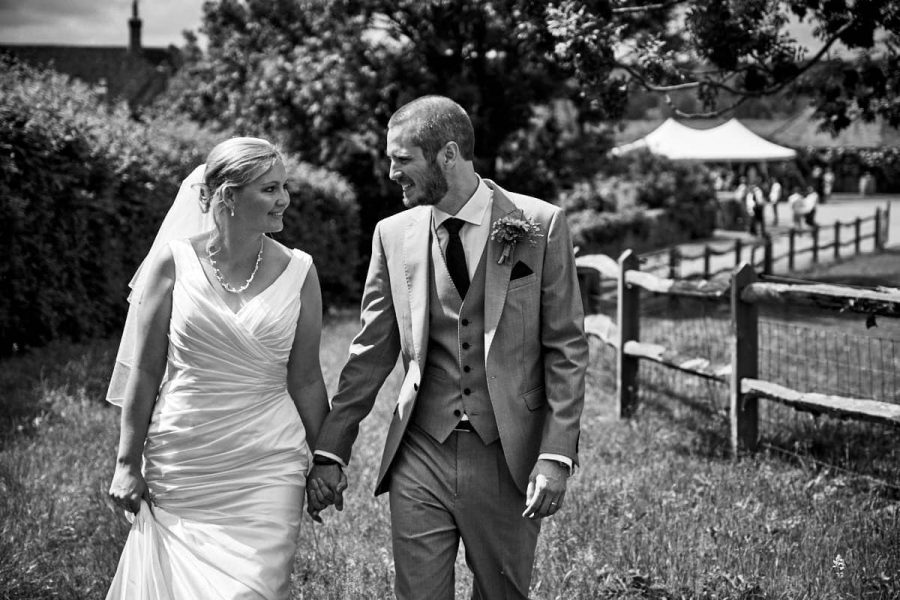 The bride and groom look at each other as they walk together at their wedding
