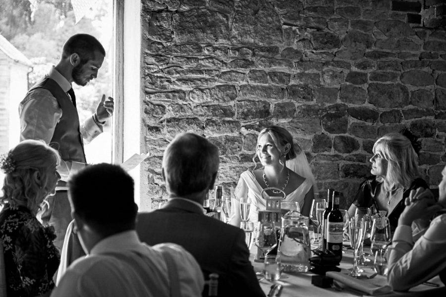 The bride looking at her groom as he does his wedding speech