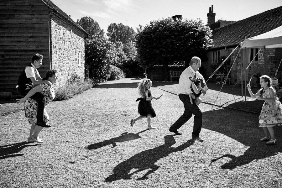 Children run around at a wedding