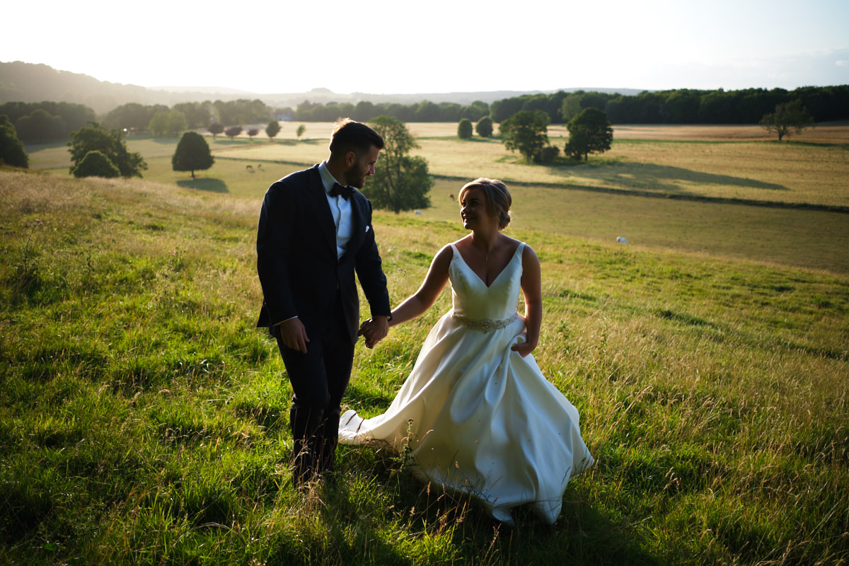 A recently married bride and groom walk across the South Downs in Sussex in the evening light.