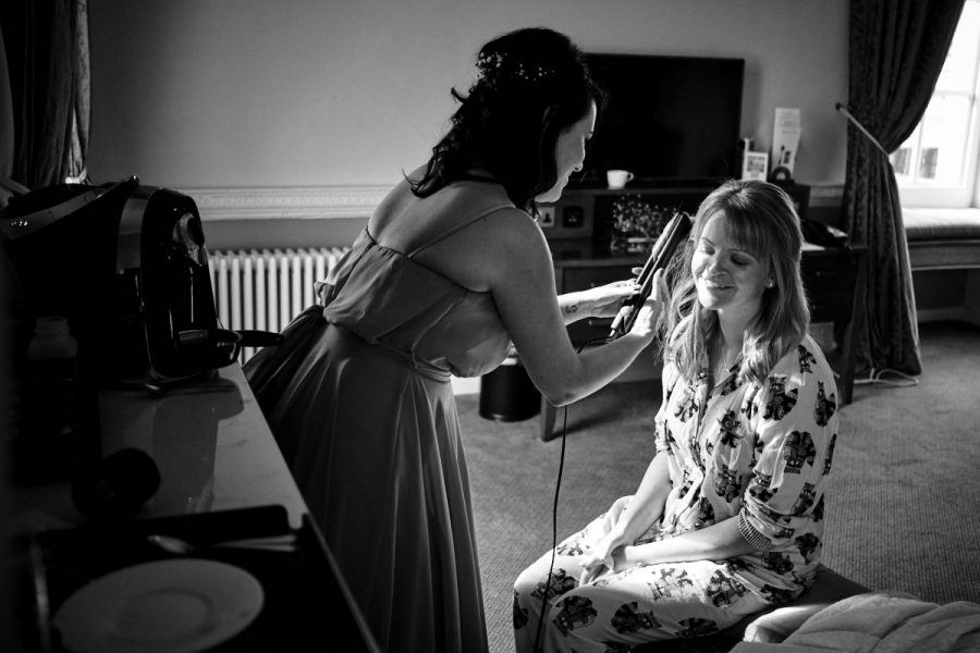 A bride having her hair straightened at her Buxted Park Hotel wedding.