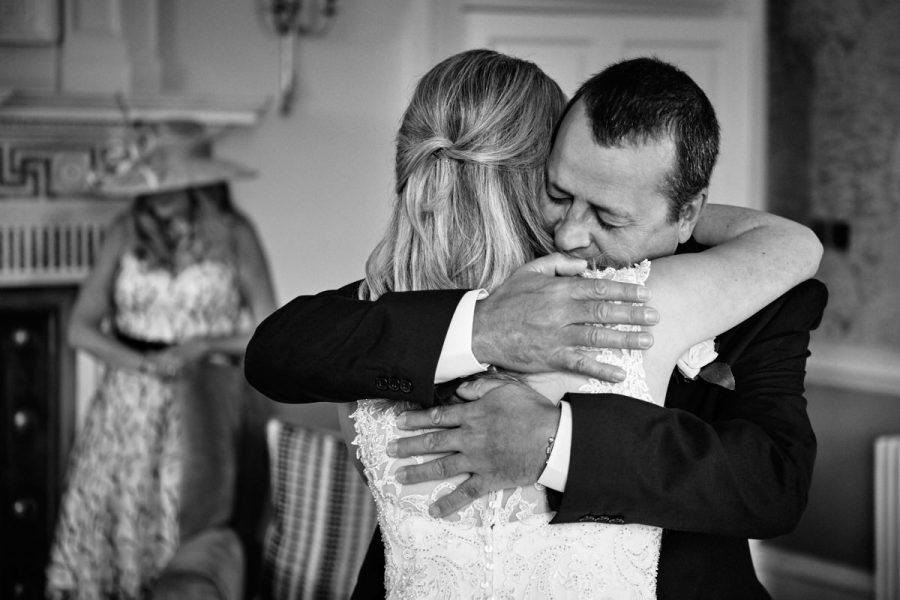 The father of the bride hugging her on her wedding day at Buxted Park Hotel.