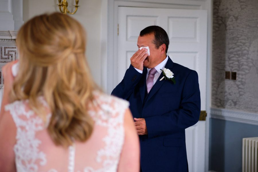 The father of the bride wiping tears from his eyes at a wedding at Buxted Park Hotel in East Sussex.
