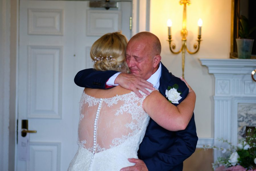 The father of the bride crying as he hugs his daughter at her wedding at Buxted Park Hotel in East Sussex.