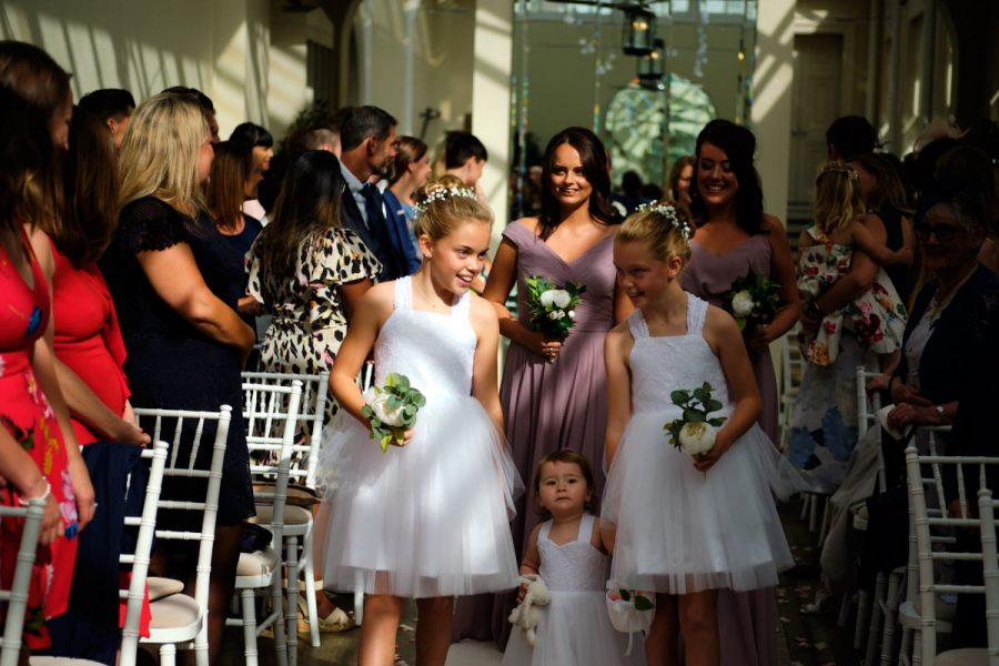 Two bridesmaids and a flower girl walk down the aisle at a wedding at Buxted Park Hotel in East Sussex.