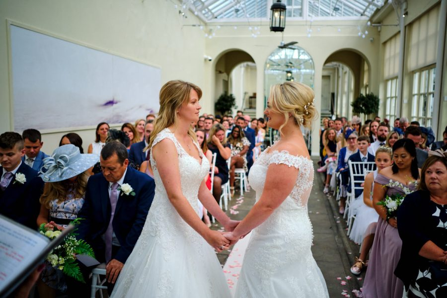 Two brides look at each other during their ceremony at their same sex wedding at Buxted Park Hotel.