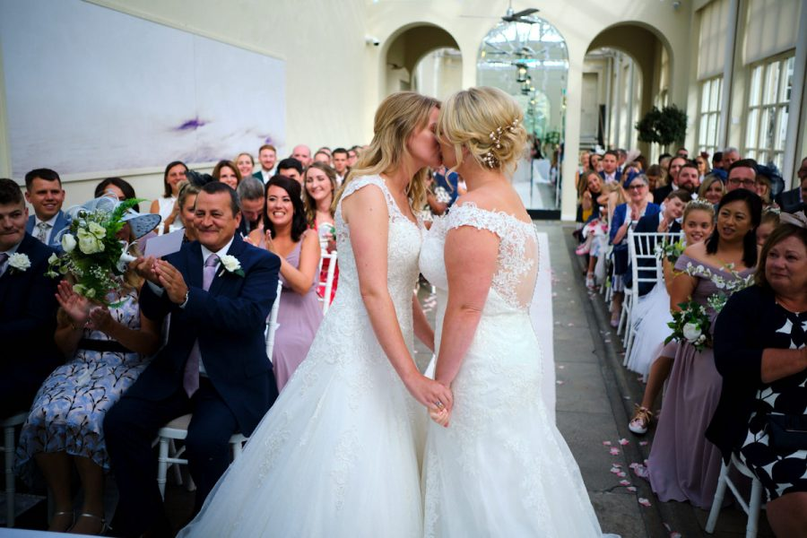 Two brides share their first married kiss at their same sex wedding at Buxted Park Hotel.